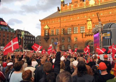 A crowd of people in the main square of Copenhagen (in front of the town hall) watching a soccer game) on a big screen in 2004 (Photo: Felix Andrews, Floybix)